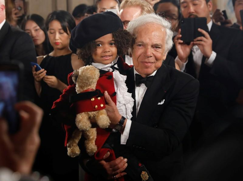 Designer Ralph Lauren holds a child model after his 50th anniversary fashion event during New York Fashion Week in New York